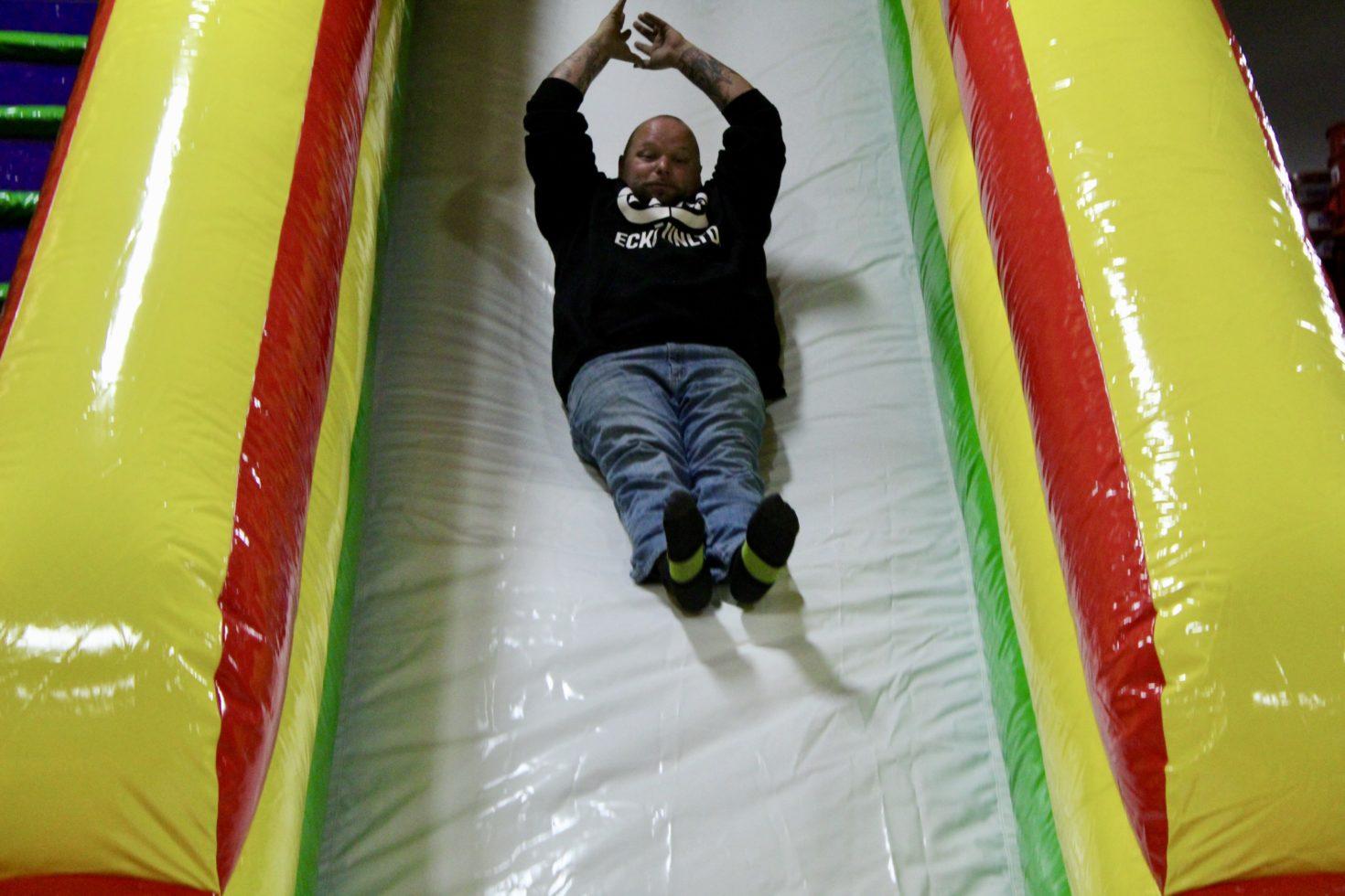 Guy sliding down commander slide